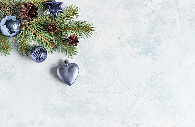Cartolina d'auguri di natale con i rami di albero di nuovo anno, i coni e le decorazioni di natale.