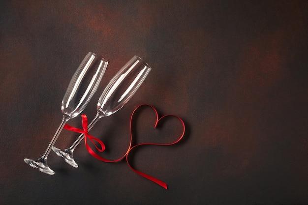 Cartolina d'auguri di san valentino con bicchieri di champagne e cuori di caramelle su fondo di pietra.