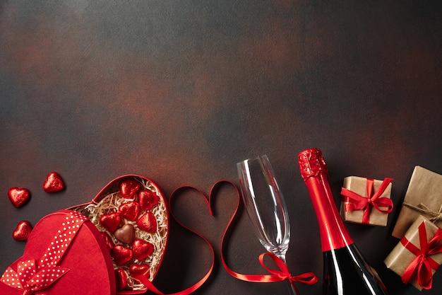 Cartolina d'auguri di san valentino con bicchieri di champagne e scatola regalo amore su fondo di pietra.