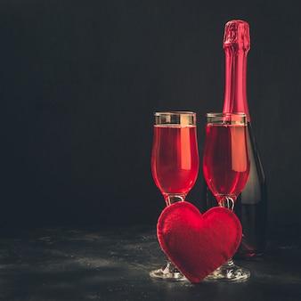 Cartolina d'auguri di san valentino e compleanno con champagne e cuore sul nero.