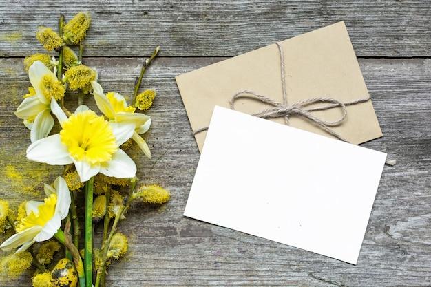 Cartolina d'auguri e busta bianche in bianco con i fiori del narciso e