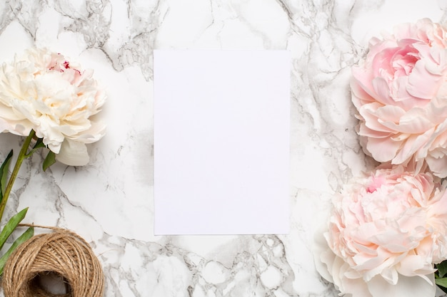 Cartolina d'auguri e peonia rosa dei fiori su una superficie di marmo. articolo per vacanze ed estate.