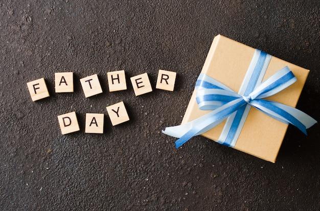 Cartolina d'auguri felice di festa del papà con il contenitore di regalo decorato su fondo scuro.