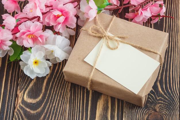Cartolina d'auguri in bianco con il mazzo dei fiori su fondo di legno