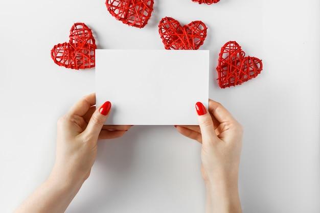 Cartolina d'auguri in mani su un bianco per il giorno di san valentino.