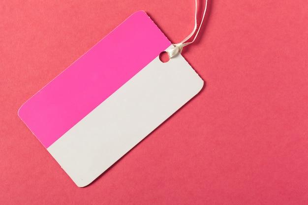 Cartolina d'auguri o etichetta in bianco su superficie rosa