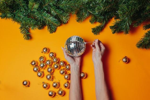 Cartolina di natale con copyspace. la donna tiene gli ornamenti di natale sull'arancia. palla da discoteca d'argento nelle mani con rami di abete verde intorno.