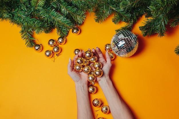 Cartolina di natale con copyspace. la donna tiene gli ornamenti dorati di natale sull'arancia. natale piatto disteso con rami di abete verde.
