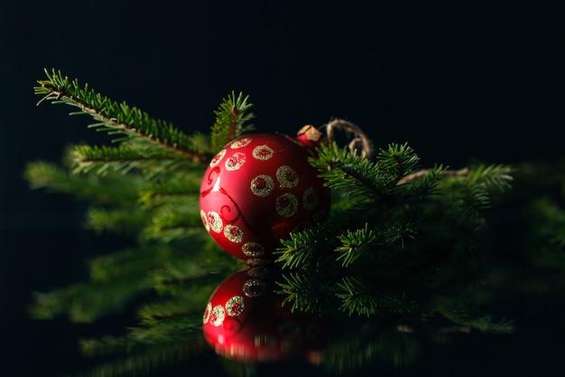 Cartolina di natale con palline rosse e albero di pelliccia su sfondo nero