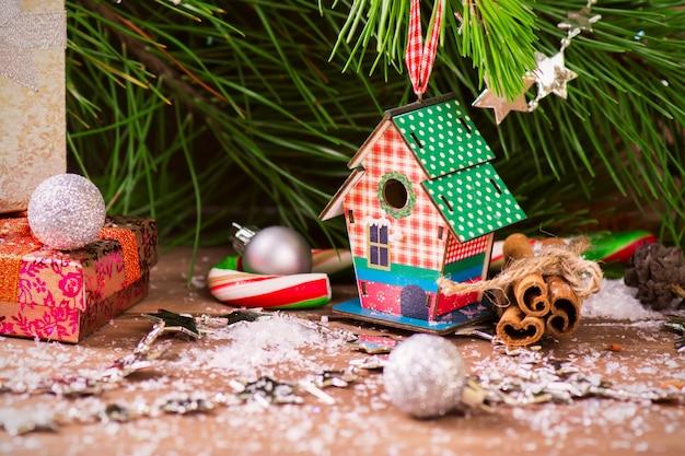 Cartolina di natale con pino, scatola di nidificazione e regali di natale su sfondo in legno vecchio