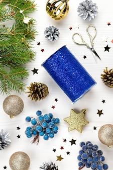 Cartolina di natale con rami di abete, scatole regalo, decorazioni dorate e blu e ornamenti in legno