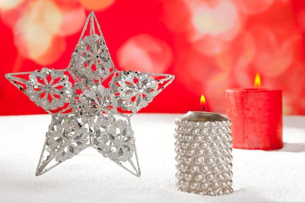 Cartolina di natale della stella d'argento e candela sulla neve