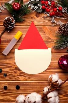Cartolina di natale fai da te passo dopo passo. da carta colorata e cotone idrofilo su un tavolo di legno.