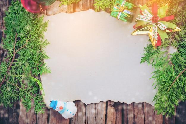 Cartolina di natale in bianco sul fondo di legno di struttura con altri che decorano gli oggetti