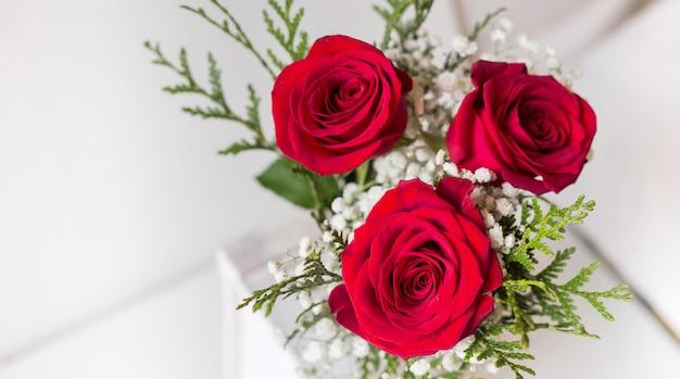 Cartolina di san valentino con tre rose naturali rosse e sfondo bianco con spazio per scrivere