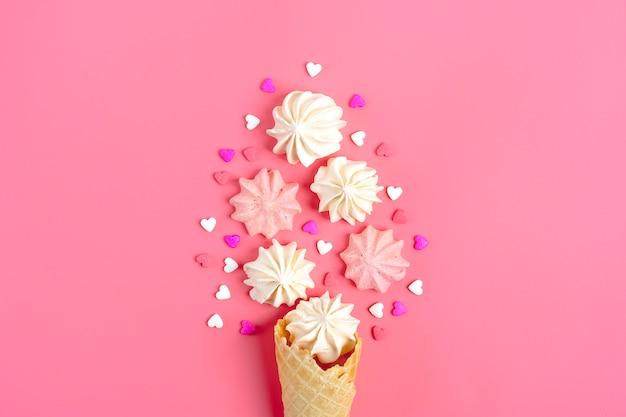 Cartolina di san valentino - meringa, caramelle a forma di cuore e cono gelato su sfondo rosa