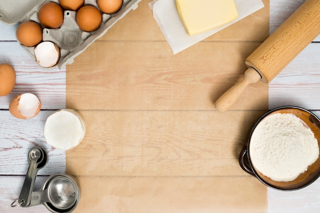 Cartone di uova; burro; mattarello; farina e misurino sul tavolo di legno