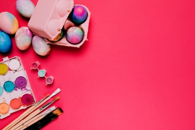 Cartone di uova colorate; tavolozza dei colori ad acqua e pennelli su sfondo rosa