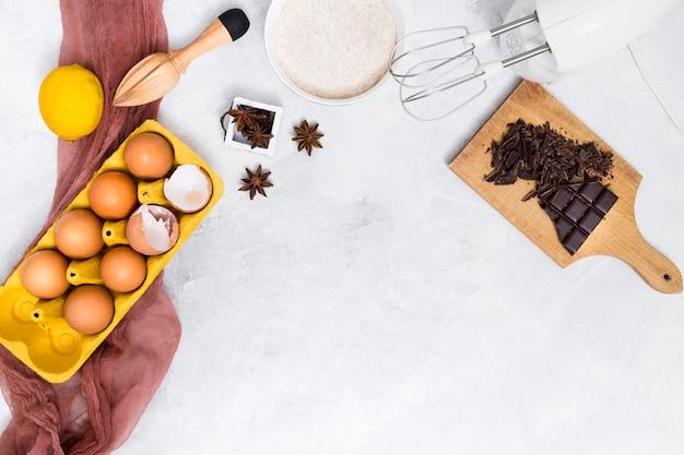 Cartone di uova; farina; limone; anice stellato; barra di cioccolato e spremiagrumi in legno su sfondo bianco