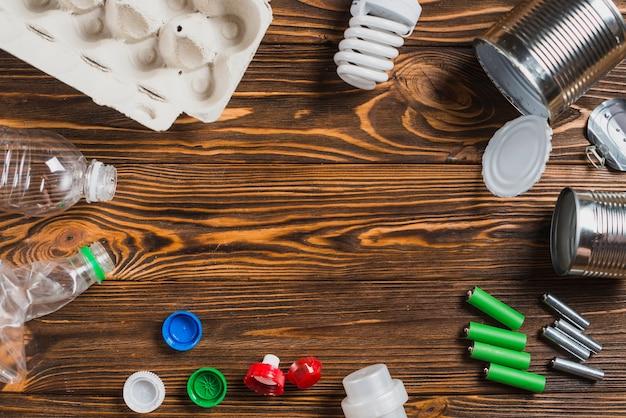 Cartone di uova; lampadina; può; batteria; cap; bottiglie su fondo in legno con texture