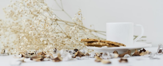Casa accogliente con una tazza di caffè e ramo di fiori. hygge stile invernale o autunnale