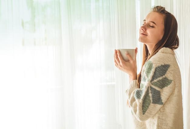 Casa accogliente. donna con una tazza di bevanda calda vicino alla finestra. guardando la finestra e bevi il tè. buongiorno con il tè. donna abbastanza giovane che si distende. felice concetto.
