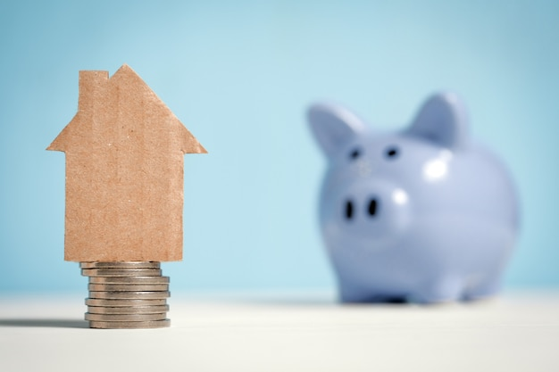 Casa astratta del cartone su una pila di monete accanto ad un porcellino salvadanaio