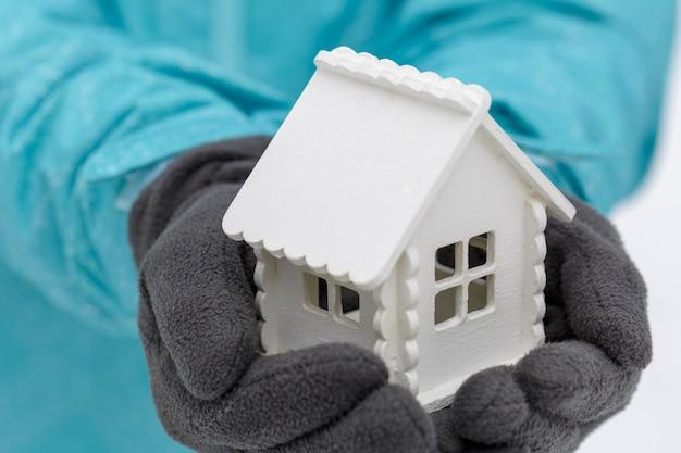 Casa bianca del giocattolo nelle mani di un uomo che indossa guanti scuri