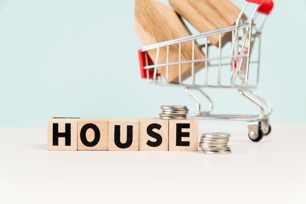 Casa blocchi di legno con una pila di monete davanti al modello di casa nel carrello