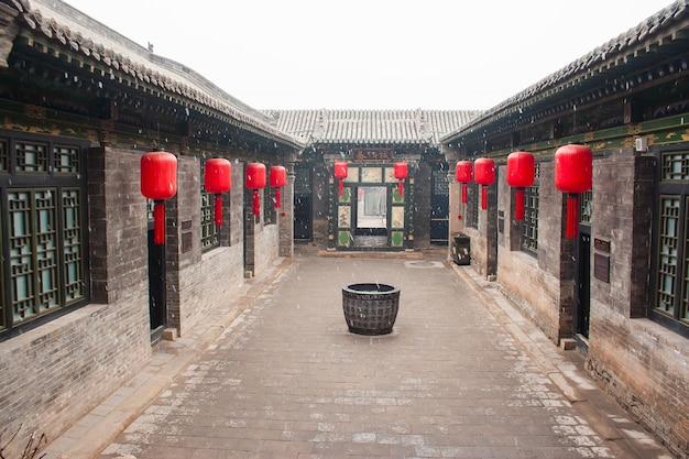 Casa cinese tradizionale con lanterne rosse e la neve
