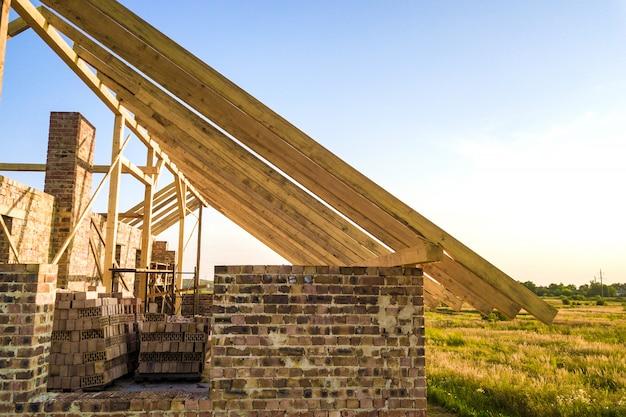 Casa con mattoni a vista non finita con la struttura di tetto di legno in costruzione.