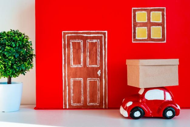 Casa decorativa rossa con auto giocattolo e scatola