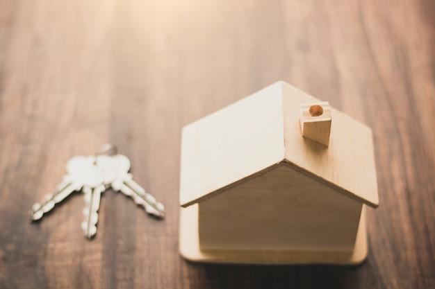 Casa del bene immobile e concetto di affari residenziali, modello della casa e posto di chiavi sulla tavola di legno