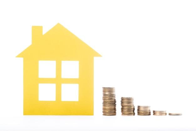 Casa del bene immobile e mucchi delle monete su fondo bianco