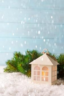 Casa del giocattolo di natale, nevica su uno sfondo naturale di un vero abete nella neve.