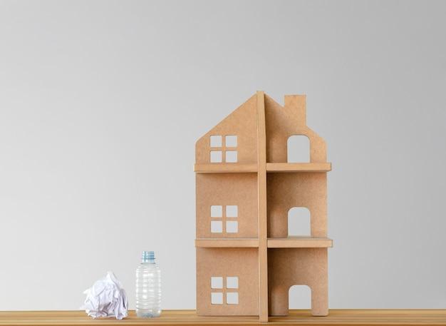 Casa del giocattolo in legno e rifiuti riciclabili