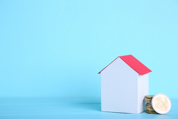 Casa del libro bianco con tetto rosso, con monete su sfondo blu