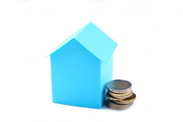 Casa della carta blu con le monete isolate su fondo bianco