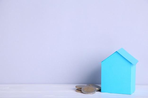 Casa della carta blu con le monete su fondo grigio