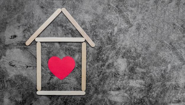 Casa di bastoni di legno del gelato creativo con cuore rosso su un vecchio muro