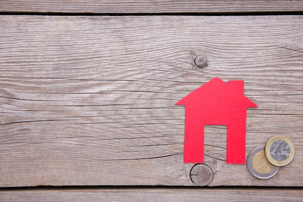 Casa di carta rossa con tetto rosso, con monete su sfondo grigio