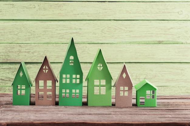 Casa di carta sulla tavola di legno verde