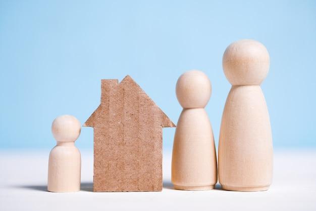 Casa di cartone astratta vicino alla famiglia: mamma, papà, bambino. proprietà domestica.
