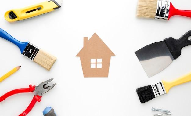 Casa di cartone con riparazione e pennelli