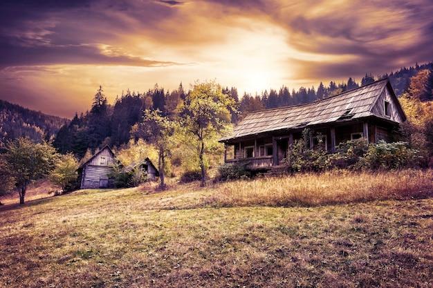 Casa di legno abbandonata sul pendio di collina sotto il cielo drammatico