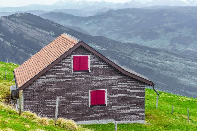 Casa di legno sull'erba verde con sfondo di vista sulle montagne