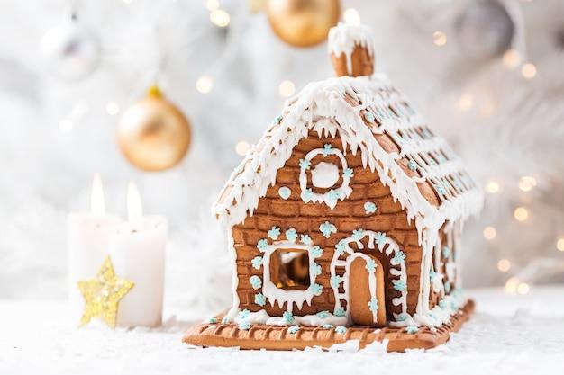 Casa di marzapane fatta in casa, candele e albero di natale