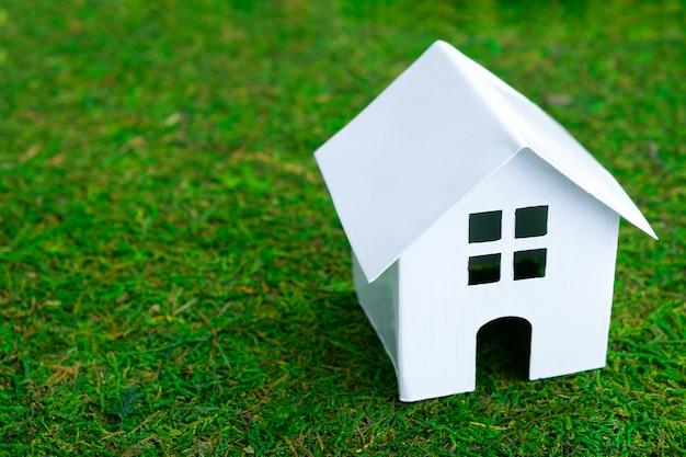 Casa di modello bianca su prato inglese decorativo verde