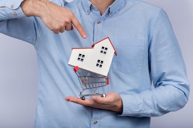 Casa di modello della tenuta dell'uomo in carrello. comprare casa concetto