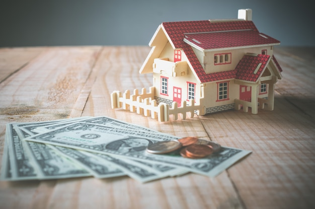 Casa di modello di legno con soldi sulla tavola di legno con lo spazio della copia pronto